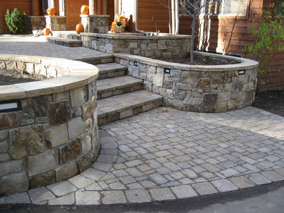paver walkway with stone stairs and stone flower beds