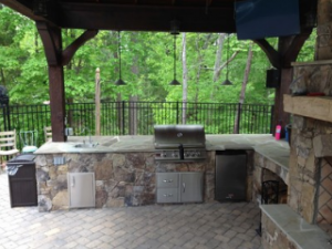 stone outdoor kitchen on backyard paver patio