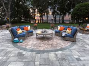 stone patio with fire pit and comfy blue chairs around it