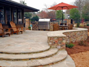 stone patio with stone retaining wall and outdoor kitchen