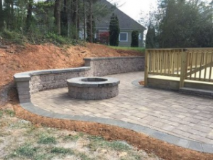 retaining wall holding back the side of a hill around paver patio